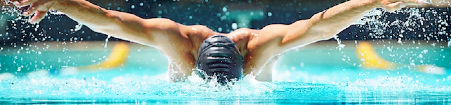 Shot of a male swimmer doing the butterfly stroke toward the camera